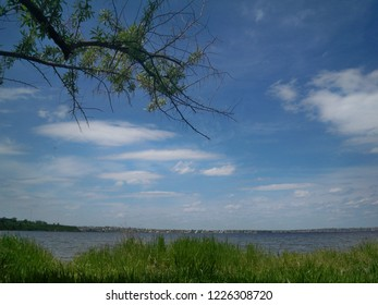 riverbank covered with grass and tree branches against pictorial sky with clouds
