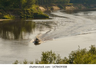 riverbank and a motor boat goes on the water, leaving a mark