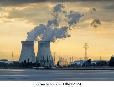 Riverbank with nuclear power plant Doel during a sunset with dramatic cluds, Port of Antwerp, Belgium