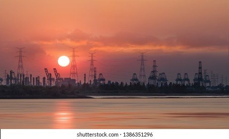 Riverbank with silhouettes of container terminal cranes during a red colored sunset, Port of Antwerp, Belgium.