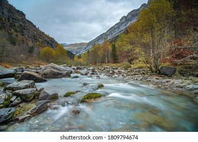 A riverbed with a mountain on the side in autumn
