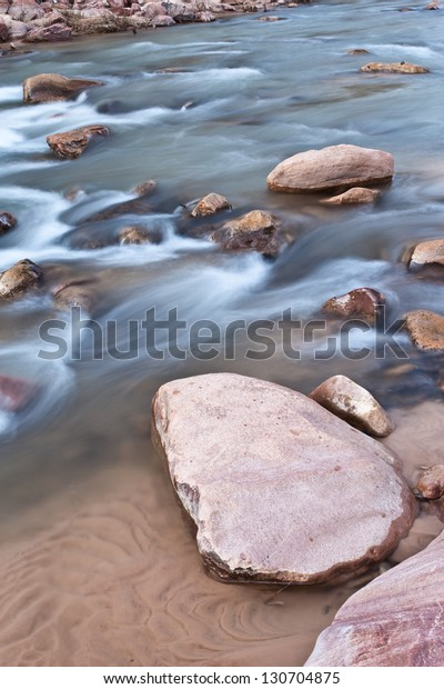 Riverbed with red rocks and soft flowing water in Zion's National Park