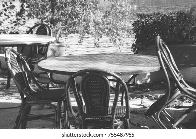 Riverside cafe. Round tables. and wicker chairs. Autumn. France. Black and white photo.