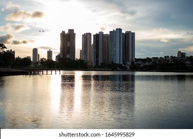 Riverside in the Park of the Nations Indigenous in Campo Grande-MS, Mato Grosso do Sul. Sunset and buildings in the background. Postcard from Cidade Morena.