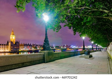 Riverside path at night with view of London