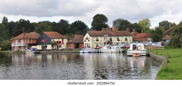 The Riverside in the village of Coltishall, Norfolk Broads, UK with boats and local pub
