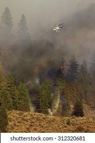 Riverside, WA, USA August 18, 2015: Okanogan Complex Wild Fire.  A helicopter negotiates its way thru heavy smoke to dump hundreds of gallons of water on burning trees and brush