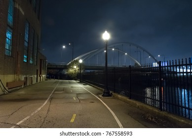 Riverwalk promenade and city bridge by an urban industrial building at the Chicago river at night.