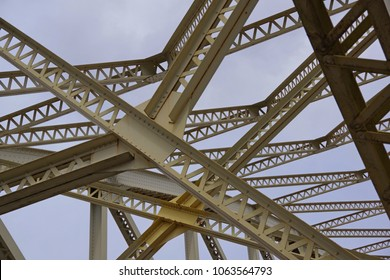 Rivets and beams of yellow bridge -  abstract closeup with blue sky as background