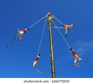 RIVIERA MAYA, MEXICO - DECEMBER 27, 2019:The Voladores, or flyers performance. They climb up a very high pole their waist to ropes wound around the pole and then jump off, flying gracefully around it.