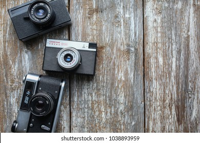 RIVNE, UKRAINE - MARCH 01, 2018: Old photo cameras on old wooden texture. Vintage film cameras on background. Retro and antique.
