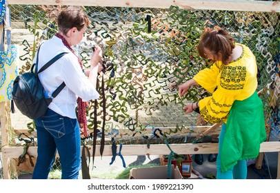 Rivne, Ukraine - May 2021: Women are weaving a camouflage net. Green mesh fence