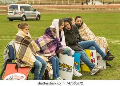 Rivne, Ukraine - Oktober 11, 2015: Girls - cheerleaders are waiting for the competition to warm themselves with blankets on the motor track in Rivne., Ukraine.