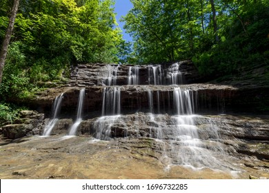Rivulets of falling water over rock ledges are topped by emerald green leaves and a deep blue sky on a summer day at Fallsville Falls, a beautiful tiered waterfall near Hillsboro, Ohio.