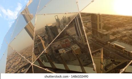 Riyadh / Saudi Arabia - August 08 2019: Reflection of the skyline of Riyadh by sunset in the Globe of Faisaliyah Tower