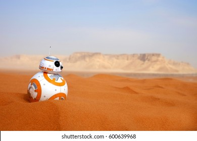 Riyadh, Saudi Arabia - December 5, 2017: Sphero's BB-8 toy on a real desert red sand dunes. It is a smartphone powered toy. BB8 was a droid introduced in the Star Wars Episode VII The Force Awakens.