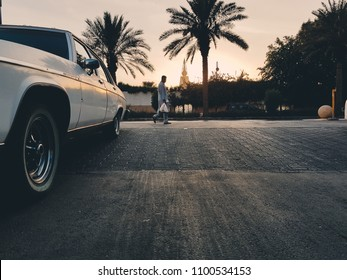 Riyadh, Saudi Arabia - May, 19 2017: A man walks past an old car downtown in Riyadh before sunset.