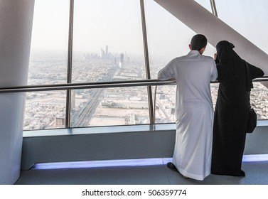 RIYADH, SAUDI ARABIA - OCTOBER 10, 2015. Saudi family men in white and his wife in black dress looking on the city from Kingdom Tower