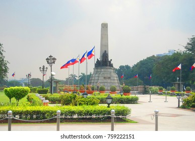 The Rizal Jose statue is blurred through several Philippine flags fluttering in the wind.