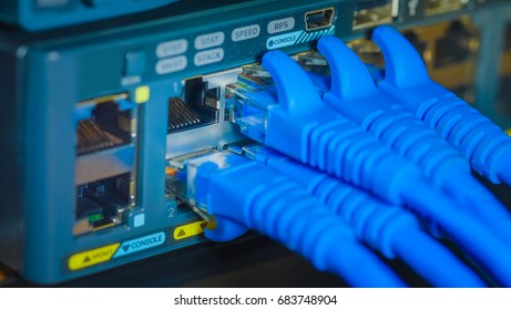 rj45 Connector or UTP port cat6 ethernet cable and Network gigabit switch in data server room. close up and blur background.