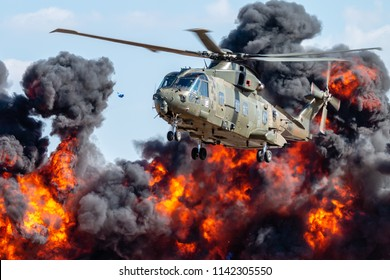 RNAS YEOVILTON, ENGLAND - July 07, 2018: A Royal Navy Merlin Helicopter and explosions as part of the Helicopter Force Role Demo at RNAS Yeovilton, England