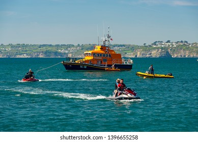 RNLI, Unknown members of the public, Logos. Polkerris, Cornwall UK, 11/05/2019. Fowey Harbours resident lifeboat pulls into the popular recreational semi harbour at Polkerris for a PR event