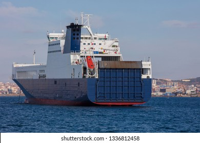 Ro ro cargo ship leaving the harbour at sunset - Image