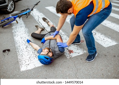 Road accident with injured cyclist lying on the pedestrian crossing near the bicycle and car, male driver providing first aid