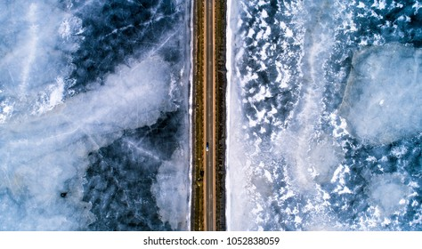 Road across frozen lake from above view. Winter transportation background.