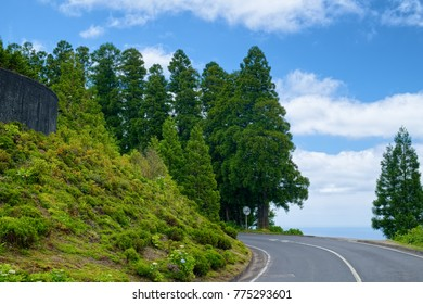 A road across mountains covered by greenery on Sao Miguel island of Azores, Portugal, with small strip of Atlantic Ocean visible at right side.