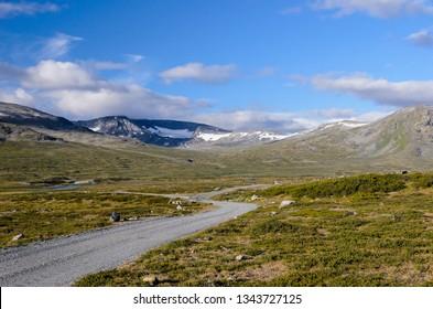 The road across the tundra feldmark along the hills with snowfields in the Jotunheimen national park