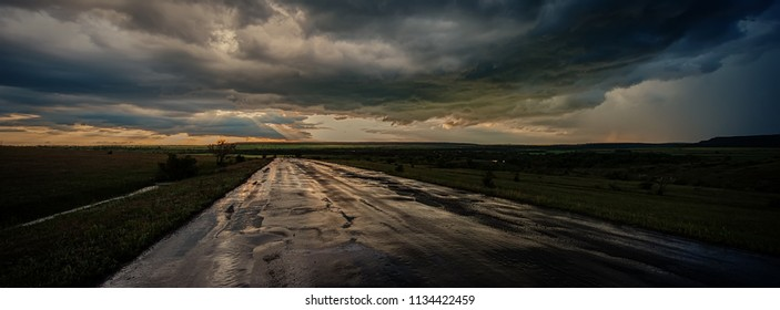 Road after the rain and evening storm clouds, panorama. Blurred background. Web banner for design.