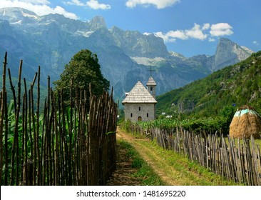 Road in the Albanian village with a small church, wooden fence, haystack and green field with mountains in the background.