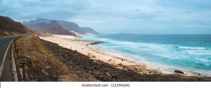 Road along atlantic coastline white sand dunes and ocean waves rolling. Road leads between black volcano erosion mountains. Breathtaking coastline of Calhau, Sao Vicente Island Cape Verde