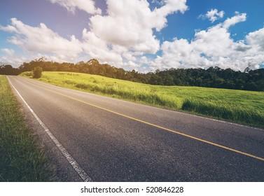 Road along hillside green grass under blue sky.