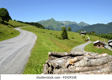 Road in the Alps mountains near Morzine in France with a pile of logs