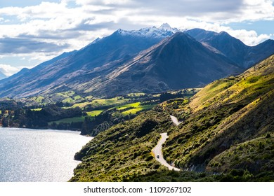 Road among the beautiful nature of the mountain and lake in Autumn on a sunny day.
