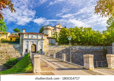 Road to Arch Gate over moat of Castello or Castle of Brescia or Falcon of Italy on Cidneo Hill with green park in historical city centre, blue cloudy sky background, Lombardy, Northern Italy