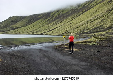 Road around Blautulón lake. The road is not going around but along banks in the water. The woman is taking picture of unusual traffic sign showing how to drive.