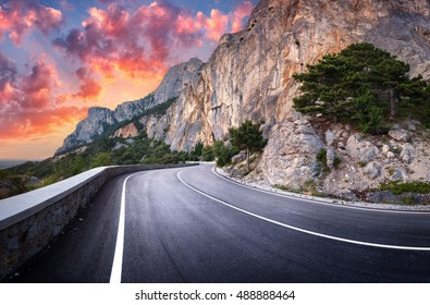 Road. Asphalt road. Colorful landscape with beautiful winding mountain road with a perfect asphalt with high rocks, amazing sky at sunset in summer. Panoramic. Beautiful road. Highway at mountains