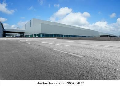 Road asphalt pavement and modern factory warehouse