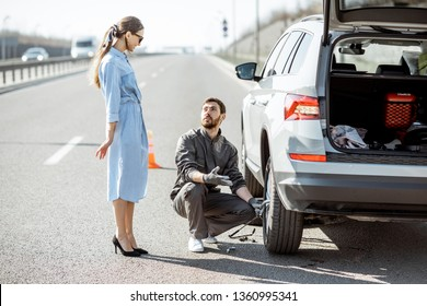 Road assistance worker helping young woman to change a car wheel on the highway