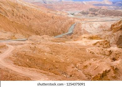 Road in the Atacama desert between salt formations at Valle de la Luna, spanish for Moon Valley, also know as Cordillera de la Sal, spanish for Salt Mountain Range, San Pedro de Atacama, Chile
