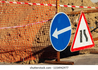 Road atention signs near the trench on the road. Repair work is underway.