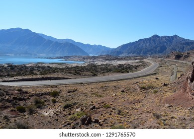 A road between arid mountains. A lake can be also seen.