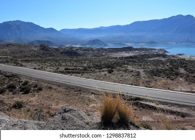 A road between arid mountains and a lake