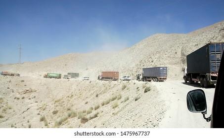 Road between Jalalabad and Kabul, Nangarhar Province / Afghanistan - Aug 16 2005: Trucks on the road between Jalalabad and Kabul in Afghanistan. A main road, dusty road in Afghanistan.