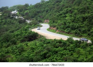 Road between lush green mountain landscape in Ayn Khor tourist resort, Salalah, Oman