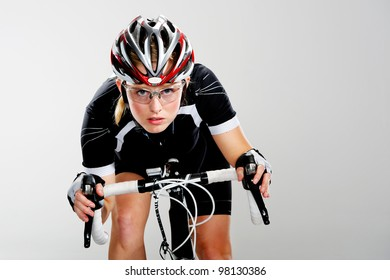 Road bicycle woman riding her bike and concentrating on winning the cycle race. full cycle gear and action as a real cyclist trains for fitness. isolated on grey.