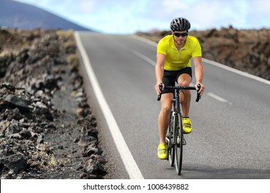 Road bike cyclist man cycling. Biking Sport fitness athlete biking on road bike. Active healthy sports lifestyle athlete cycling outside training for triathlon.
